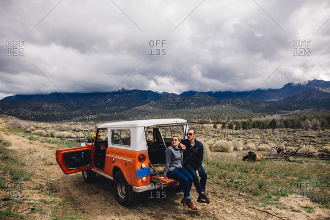 Couple with vehicle on scrubland by mountains, Kennedy Meadows, California, USA