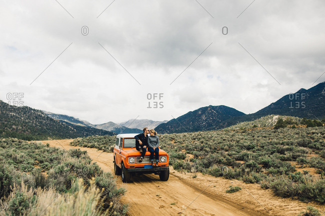 Couple sitting on vehicle in scrubland by mountains, Kennedy Meadows, California, USA