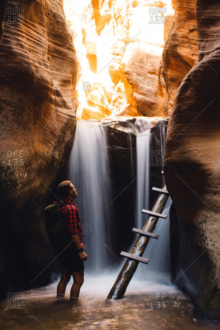 Hiker in sandstone cave by waterfall, Kanarraville, Utah, USA