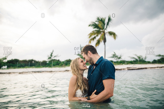 Couple waist deep in water face to face smiling