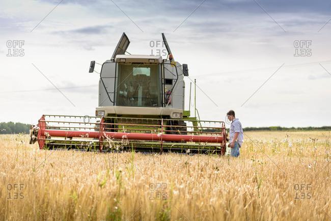 Farmer inspecting combine harvester in field of organic barley