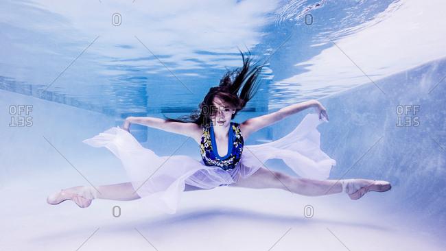 Underwater view of teenage girl, wearing ballet shoes, in dance position