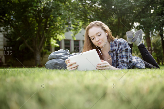 Surface level view of young woman lying in park listening to music on earphones and browsing digital tablet