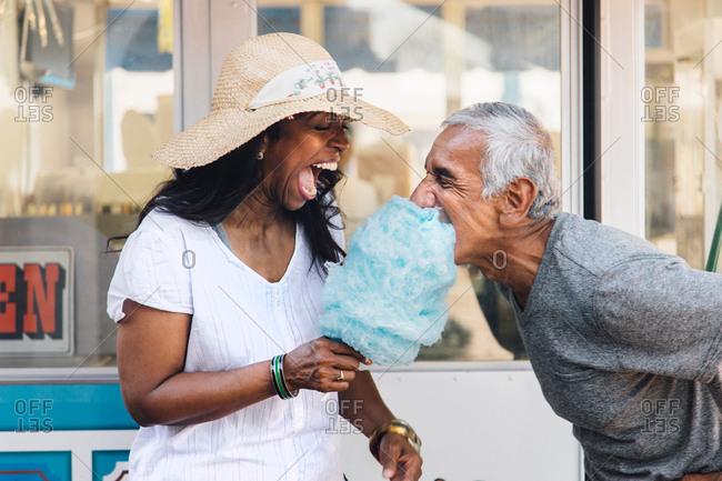 Senior couple eating cotton candy, laughing, Long Beach, California, USA