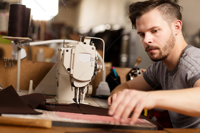 Man using sewing machine to sew leather in leather jacket manufacturers