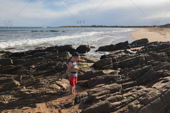 Boy standing in rocky tidal pool