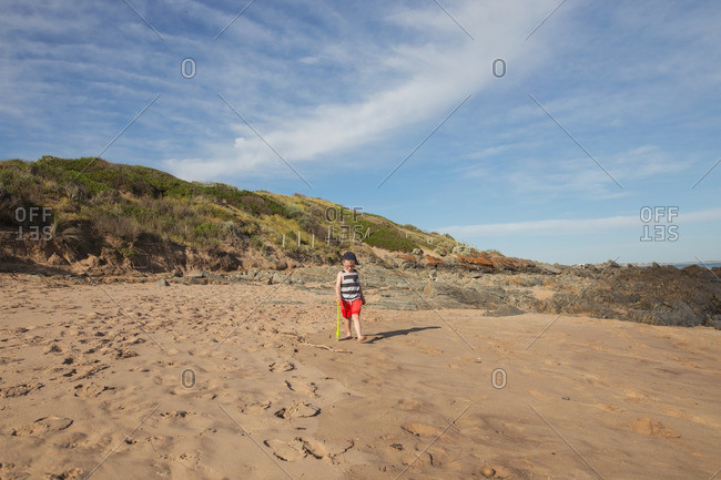 Boy strolling on coastal sand