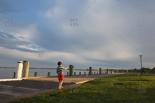 Boy on a coastal boardwalk