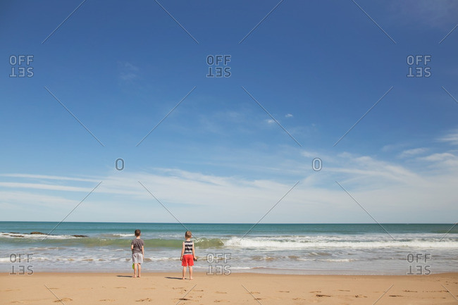 Two boys standing on a beach