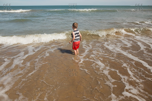 Boy in the tide in ocean