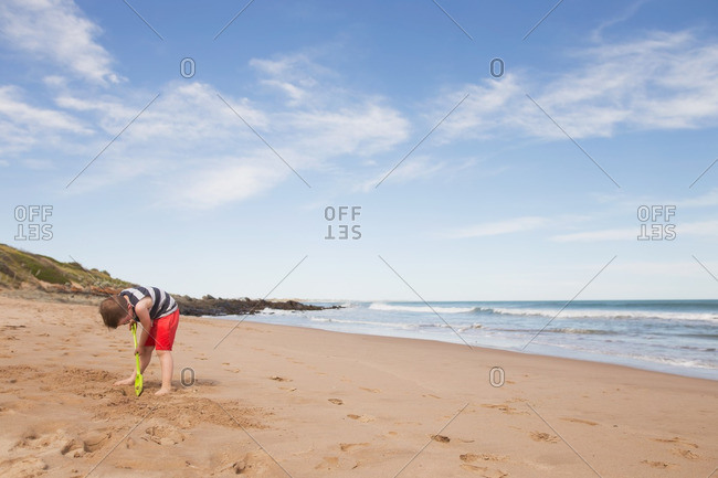 Boy digging on beach in sand