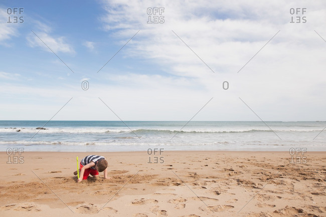 Boy digging in the sand of a beach