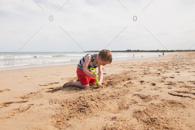 Boy digging in the beach sand