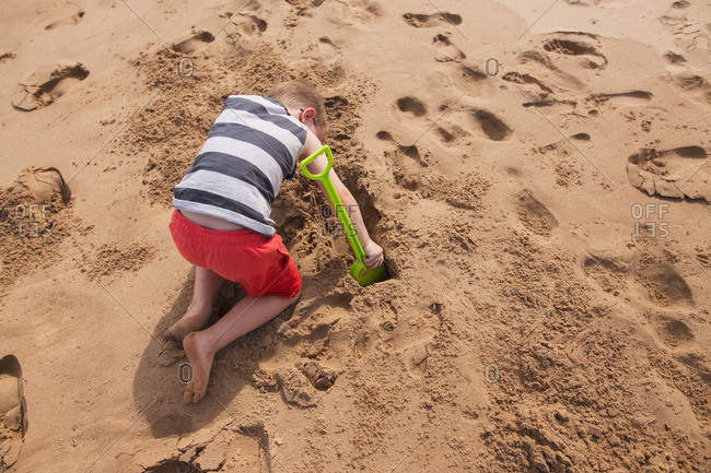Boy digging in beach sand