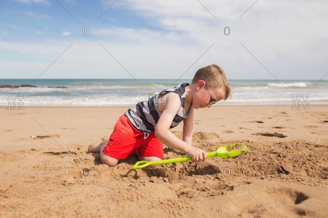 A boy digging in beach sand