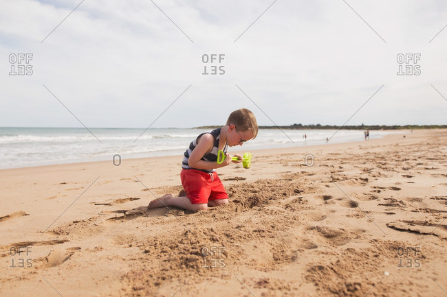 A boy digging in the beach sand