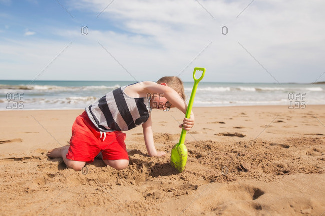 A boy digging in beach's sand