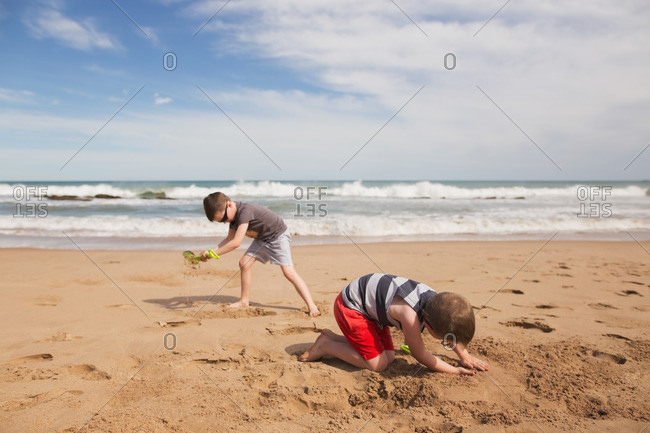 Boys playing and digging in sand