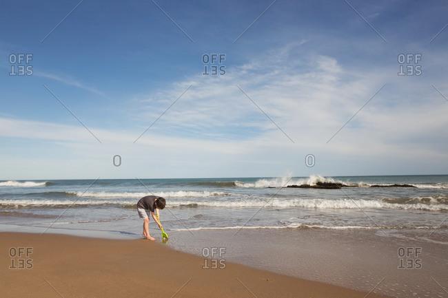 Boy digging in ocean surf