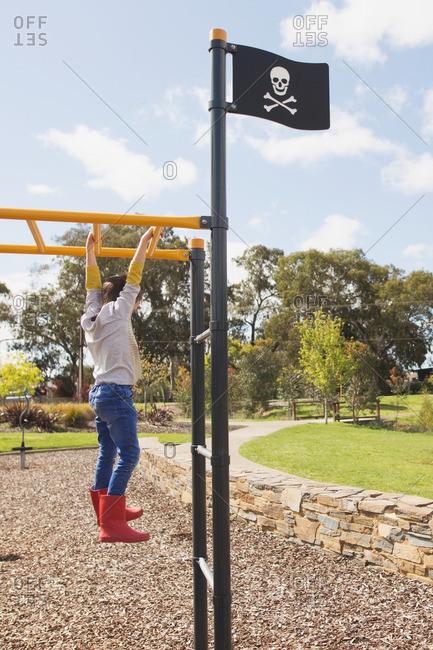 Boy dangling from monkey bars