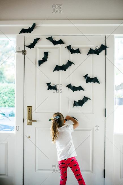 Little girl hanging bat decorations near a front door