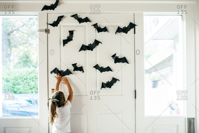 Girl reaching to touch bat decorations at her front door