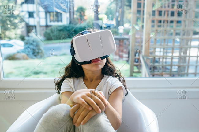 Girl in a chair experiencing a virtual reality device