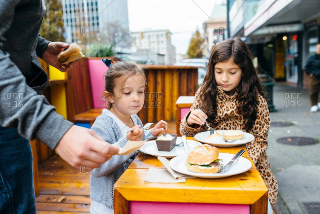 Father and two daughters enjoying bakery streets on sidewalk tables