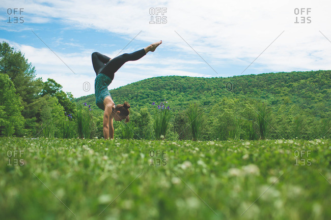 Woman doing yoga handstand in a grassy meadow