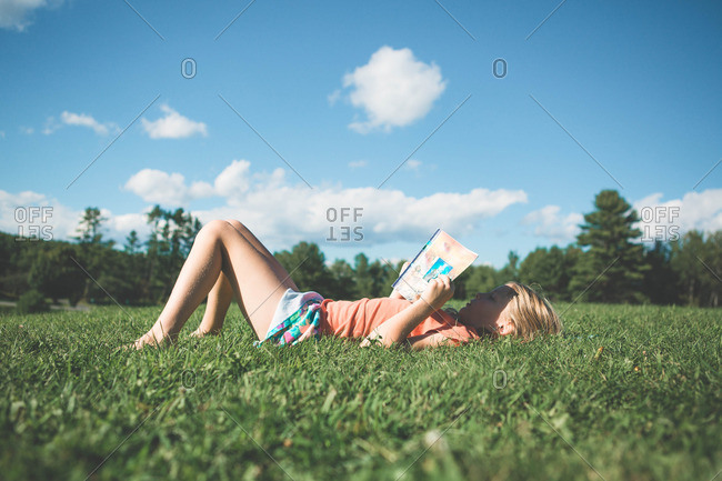 Girl lying in the grass reading a book