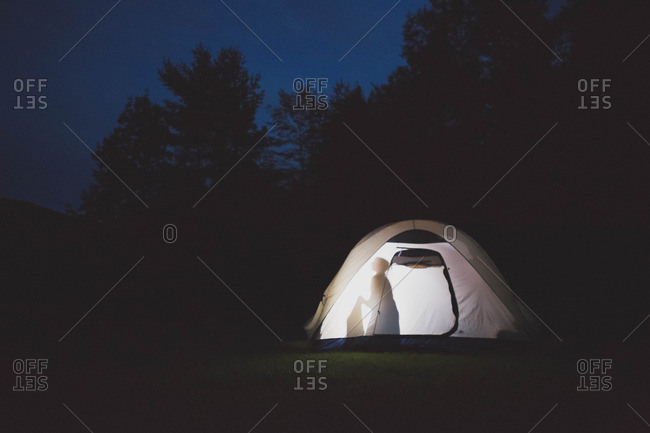 Silhouette of child in a tent at night