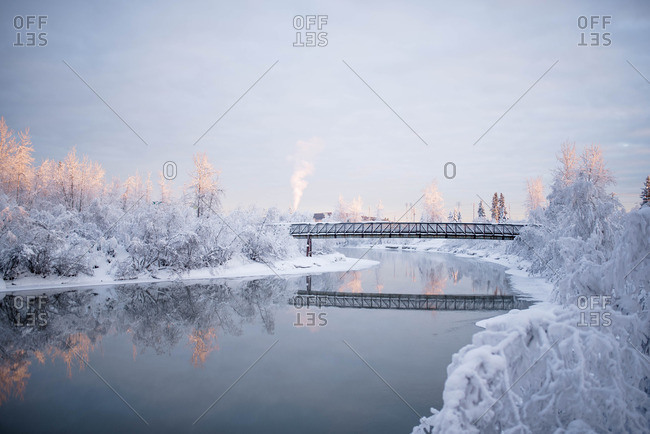 Train trestle over river in winter