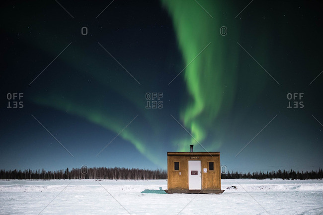 Ice fishing hut under Northern Lights
