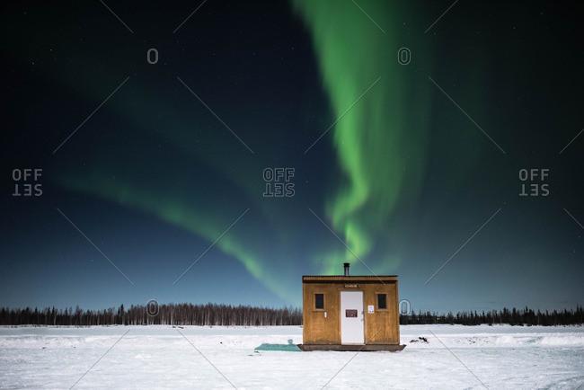 Ice fishing hut under Northern Lights