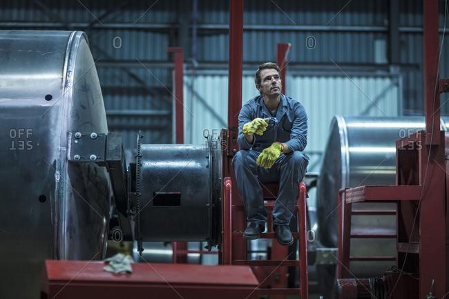 Factory worker sitting on large steel tanker