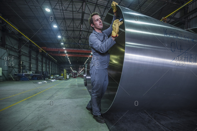 Factory worker writing something on steel cylinder in tanker factory