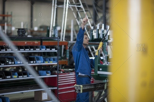 Factory worker preparing to push button on a machine