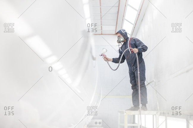 Industrial worker spray painting truck container in manufacturing factory