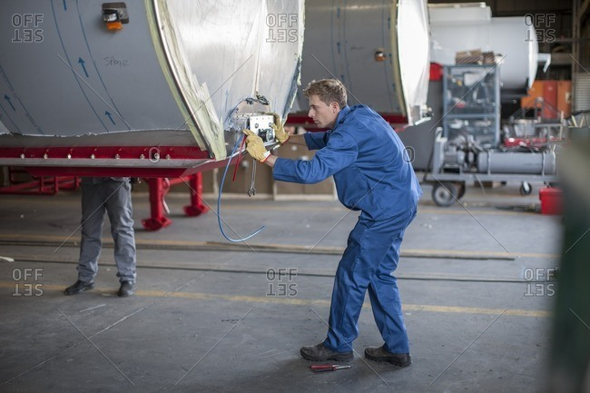 Technician installing electrical wires into truck container in a factory