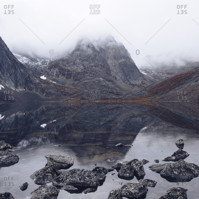 Rugged mountain landscape enveloped by clouds reflected in lake