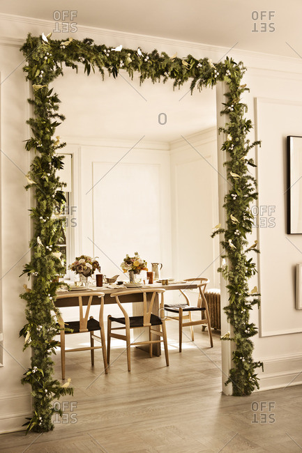 Doorway to dining area decorated with pine garland