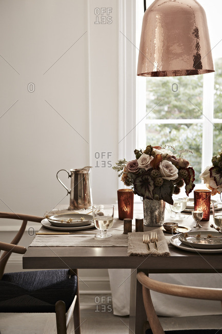 Table setting with floral arrangement, plates, and pitcher