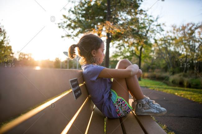 Girl resting on park bench in sunlight