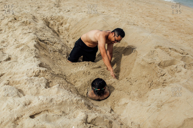 Boy being buried in sand by his father at the beach