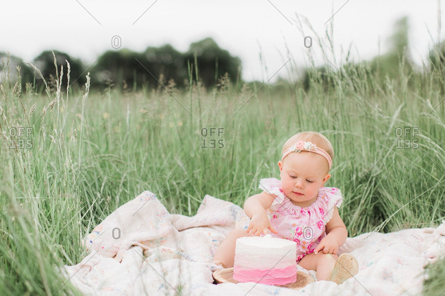 Toddler girl sticking her fingers in the icing of a birthday cake is sitting on a blanket in a meadow