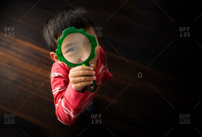 Young boy looking through a toy magnifying glass
