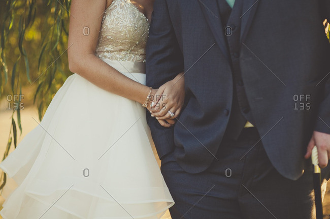 Close-up of bride with her arms around the arm of a man
