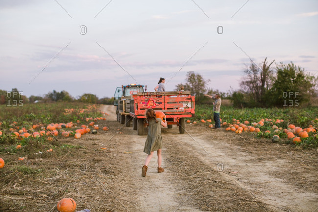 Girl carrying a pumpkin while walking down a dirt road at the pumpkin patch