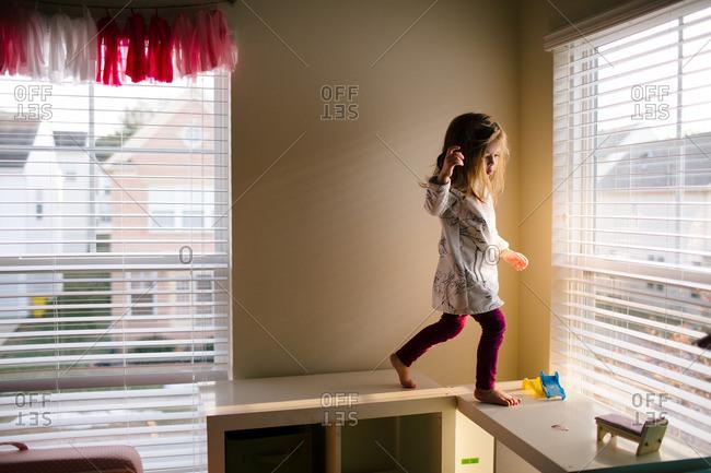 Girl walking on top of shelves in room