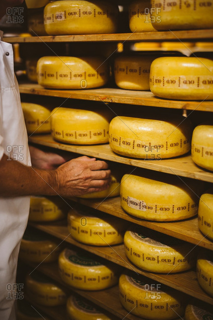 Cheesemaker with wheels of cheese on shelf